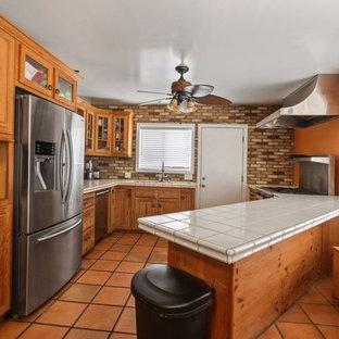 ロサンゼルスのトラディショナルスタイルのおしゃれなキッチン (トリプルシンク、シェーカースタイル扉のキャビネット、ヴィンテージ仕上げキャビネット、タイルカウンター、マルチカラーのキッチンパネル、レンガのキッチンパネル、シルバーの調理設備、テラコッタタイルの床、オレンジの床、ベージュのキッチンカウンター) の写真