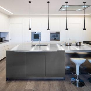Diseño de cocina en U, contemporánea, con fregadero bajoencimera, armarios con paneles lisos, puertas de armario blancas, encimera de acero inoxidable, salpicadero blanco, electrodomésticos de acero inoxidable, suelo de madera en tonos medios, una isla, suelo marrón y encimeras grises