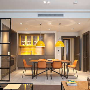 This is an example of a mid-sized contemporary l-shaped eat-in kitchen in Barcelona with flat-panel cabinets, grey cabinets, yellow splashback, ceramic splashback, light hardwood floors and no island.