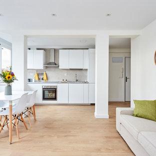 Ejemplo de cocina lineal, contemporánea, abierta, sin isla, con armarios con paneles lisos, puertas de armario blancas, electrodomésticos de acero inoxidable, suelo de madera clara, suelo beige y encimeras grises