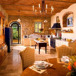 Modelo de cocina mediterránea con armarios estilo shaker, puertas de armario amarillas, electrodomésticos de colores y suelo beige