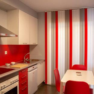 他の地域の中サイズのコンテンポラリースタイルのおしゃれなキッチン (一体型シンク、フラットパネル扉のキャビネット、白いキャビネット、ラミネートカウンター、赤いキッチンパネル、白い調理設備、磁器タイルの床、黒い床、グレーのキッチンカウンター) の写真