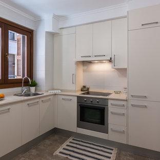 Imagen de cocina en L, contemporánea, sin isla, con fregadero encastrado, armarios con paneles lisos, puertas de armario blancas, salpicadero blanco, electrodomésticos con paneles, suelo gris y encimeras beige