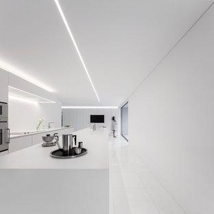 Diseño de cocina lineal, actual, extra grande, abierta, con armarios con paneles lisos, puertas de armario blancas, salpicadero blanco, electrodomésticos de acero inoxidable, una isla y encimeras blancas
