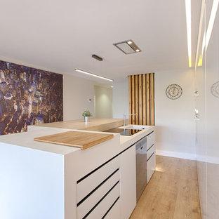 Foto de cocina de galera, contemporánea, de tamaño medio, con armarios con paneles lisos, puertas de armario blancas, encimera de madera, una isla, fregadero integrado, electrodomésticos de acero inoxidable, suelo de madera clara y suelo beige
