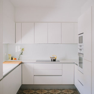 Photo of a small modern u-shaped kitchen in Valencia with flat-panel cabinets, white cabinets, white splashback, no island, multi-coloured floor and white benchtop.