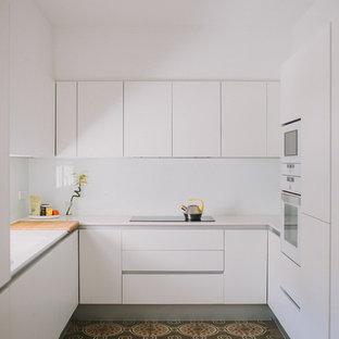 Imagen de cocina en U, moderna, pequeña, sin isla, con armarios con paneles lisos, puertas de armario blancas, salpicadero blanco, suelo multicolor y encimeras blancas