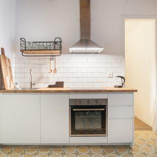 Idéer för att renovera ett litet medelhavsstil kök och matrum, med släta luckor, träbänkskiva, rostfria vitvaror och gult golv