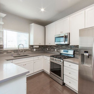 Photo of a medium sized modern single-wall open plan kitchen in Los Angeles with an integrated sink, flat-panel cabinets, white cabinets, granite worktops, multi-coloured splashback, matchstick tiled splashback, stainless steel appliances, plywood flooring, a breakfast bar, brown floors and grey worktops.