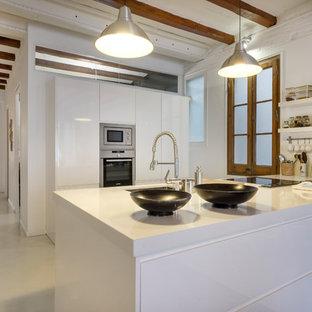 Diseño de cocina lineal, mediterránea, grande, abierta, con armarios con paneles lisos, puertas de armario blancas, electrodomésticos de acero inoxidable, península, encimeras blancas, fregadero bajoencimera, suelo de cemento y suelo gris