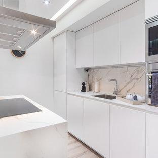 Ejemplo de cocina de galera, contemporánea, con fregadero bajoencimera, armarios con paneles lisos, puertas de armario blancas, electrodomésticos de acero inoxidable, suelo de madera clara, una isla, suelo beige y encimeras blancas