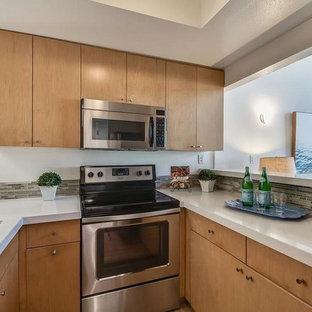 ロサンゼルスの小さいエクレクティックスタイルのおしゃれなキッチン (ダブルシンク、フラットパネル扉のキャビネット、中間色木目調キャビネット、人工大理石カウンター、マルチカラーのキッチンパネル、ボーダータイルのキッチンパネル、シルバーの調理設備の、無垢フローリング、ベージュの床、白いキッチンカウンター) の写真