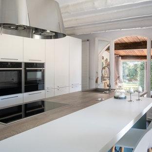 他の地域の大きい地中海スタイルのおしゃれなキッチン (ドロップインシンク、フラットパネル扉のキャビネット、ターコイズのキャビネット、ラミネートカウンター、シルバーの調理設備の、スレートの床、黒い床、ベージュのキッチンカウンター) の写真