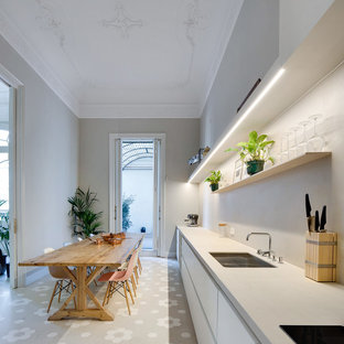Modelo de cocina comedor lineal, mediterránea, grande, sin isla, con fregadero bajoencimera, armarios con paneles lisos, puertas de armario blancas, encimeras grises y suelo gris