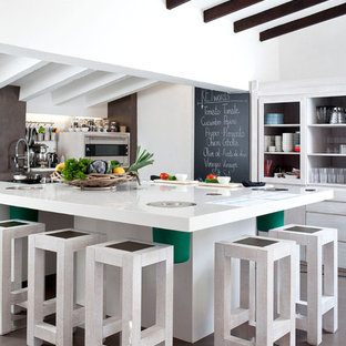 Large mediterranean enclosed kitchen pictures - Enclosed kitchen - large mediterranean l-shaped concrete floor enclosed kitchen idea in Madrid with open cabinets, white cabinets, an island, solid surface countertops and stainless steel appliances