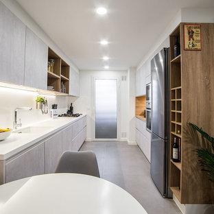 Diseño de cocina comedor de galera, actual, sin isla, con armarios con paneles lisos, salpicadero blanco, encimeras blancas, fregadero bajoencimera, puertas de armario grises, electrodomésticos de acero inoxidable y suelo gris
