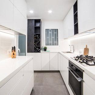 Diseño de cocina en L, contemporánea, sin isla, con fregadero de doble seno, armarios con paneles lisos, puertas de armario blancas, salpicadero blanco, electrodomésticos negros, suelo gris y encimeras blancas