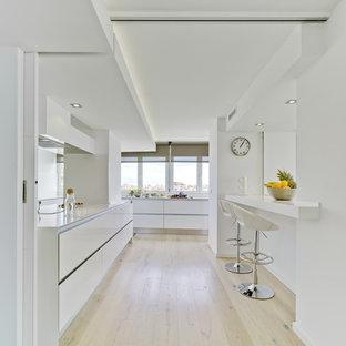 Foto de cocina de galera, costera, grande, abierta, sin isla, con armarios con paneles lisos, puertas de armario blancas, salpicadero blanco y suelo de madera clara