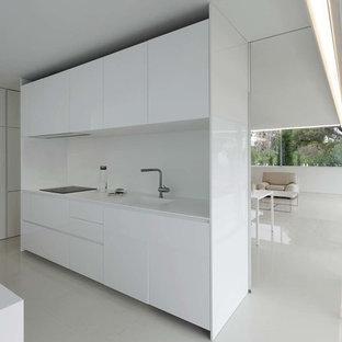 Diseño de cocina lineal, moderna, abierta, sin isla, con fregadero integrado, armarios con paneles lisos, puertas de armario blancas, salpicadero blanco, encimeras blancas, electrodomésticos con paneles y suelo blanco