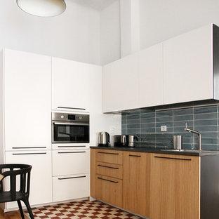 マドリードの小さいコンテンポラリースタイルのおしゃれなキッチン (シングルシンク、フラットパネル扉のキャビネット、中間色木目調キャビネット、青いキッチンパネル、セラミックタイルのキッチンパネル、パネルと同色の調理設備、セメントタイルの床、赤い床) の写真