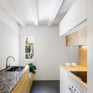 バルセロナの中サイズのインダストリアルスタイルのおしゃれなキッチン (アンダーカウンターシンク、フラットパネル扉のキャビネット、中間色木目調キャビネット、大理石カウンター、白いキッチンパネル、白い調理設備、アイランドなし) の写真
