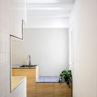 バルセロナの中サイズのインダストリアルスタイルのおしゃれなキッチン (アンダーカウンターシンク、フラットパネル扉のキャビネット、中間色木目調キャビネット、白いキッチンパネル、白い調理設備、アイランドなし) の写真