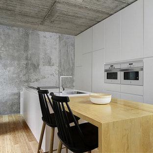 Стильный дизайн: линейная кухня в стиле модернизм с врезной раковиной, плоскими фасадами, белыми фасадами, столешницей из дерева, белой техникой, полом из бамбука, островом, бежевым полом и бежевой столешницей - последний тренд