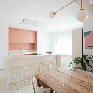 Bild på ett funkis vit vitt kök, med släta luckor, vita skåp, rosa stänkskydd, en köksö och vitt golv
