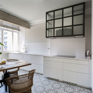 Photo of a mid-sized transitional single-wall eat-in kitchen in Other with an undermount sink, flat-panel cabinets, white cabinets, white splashback, black appliances, ceramic floors, no island, multi-coloured floor and subway tile splashback.