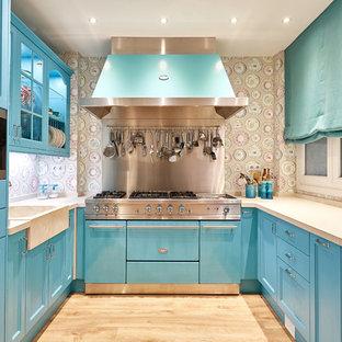 Foto de cocina en U, tradicional renovada, de tamaño medio, cerrada, con puertas de armario azules, salpicadero multicolor, electrodomésticos de acero inoxidable, suelo de madera clara y suelo beige