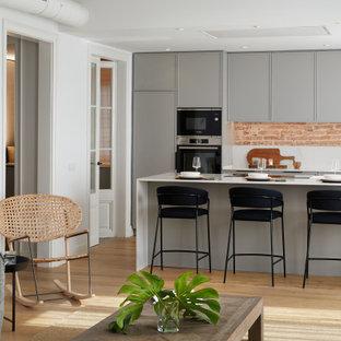 Diseño de cocina de galera, contemporánea, de tamaño medio, abierta, con fregadero bajoencimera, armarios con paneles empotrados, puertas de armario grises, salpicadero multicolor, electrodomésticos con paneles, una isla, suelo beige y encimeras blancas