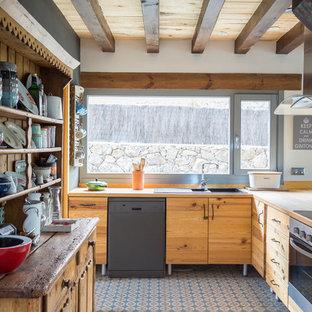 Foto de cocina en L, de estilo de casa de campo, con armarios con paneles lisos, puertas de armario de madera oscura, salpicadero blanco, electrodomésticos de acero inoxidable y suelo azul