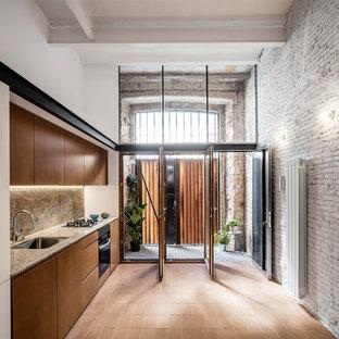 Einzeilige, Mittelgroße Moderne Küche ohne Insel mit flächenbündigen Schrankfronten, braunen Schränken, Terrakottaboden, rotem Boden, Waschbecken, Küchenrückwand in Braun und schwarzen Elektrogeräten in Barcelona