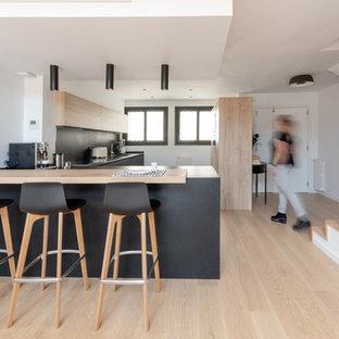 Modelo de cocina en L, escandinava, abierta, con armarios con paneles lisos, puertas de armario de madera clara, salpicadero negro, suelo de madera clara, península, suelo beige y encimeras negras