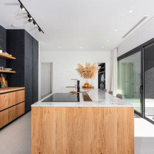 Modelo de cocina de galera, actual, extra grande, con fregadero bajoencimera, armarios con paneles lisos, puertas de armario negras, encimera de madera, electrodomésticos con paneles, una isla, suelo gris y encimeras beige