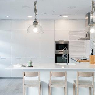 Ejemplo de cocina actual con fregadero de un seno, armarios con paneles lisos, puertas de armario blancas, electrodomésticos de acero inoxidable, suelo de madera clara, península y suelo beige