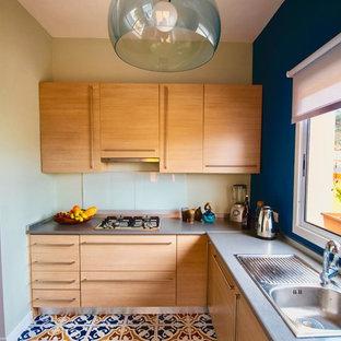 他の地域の小さいエクレクティックスタイルのおしゃれなキッチン (ドロップインシンク、中間色木目調キャビネット、ラミネートカウンター、白いキッチンパネル、ガラスまたは窓のキッチンパネル、白い調理設備、セラミックタイルの床、グレーのキッチンカウンター) の写真