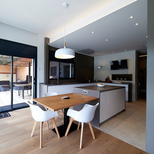 Design ideas for a large modern l-shaped open plan kitchen in Barcelona with an undermount sink, flat-panel cabinets, brown cabinets, marble benchtops, brown splashback, marble splashback, black appliances, porcelain floors, with island, beige floor and brown benchtop.