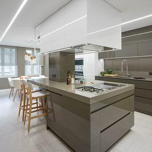 Imagen de cocina comedor en L, actual, con fregadero bajoencimera, armarios con paneles lisos, puertas de armario grises, salpicadero verde, electrodomésticos con paneles, una isla, suelo gris y encimeras grises