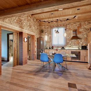 Imagen de cocina lineal, rural, abierta, con armarios con paneles lisos, puertas de armario de madera clara, electrodomésticos de acero inoxidable y suelo de madera clara