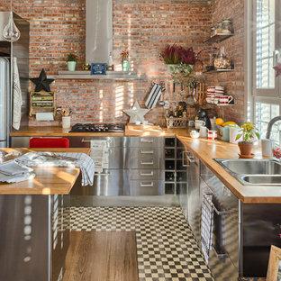 マドリードの広いインダストリアルスタイルのおしゃれなキッチン (ドロップインシンク、フラットパネル扉のキャビネット、ステンレスキャビネット、木材カウンター、シルバーの調理設備、無垢フローリング) の写真