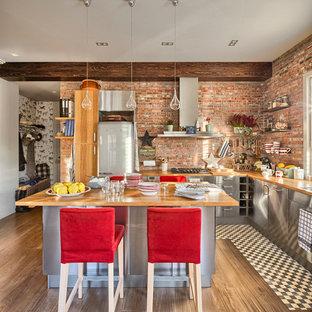 マドリードの大きいインダストリアルスタイルのおしゃれなキッチン (フラットパネル扉のキャビネット、ステンレスキャビネット、木材カウンター、オレンジのキッチンパネル、シルバーの調理設備の、無垢フローリング) の写真