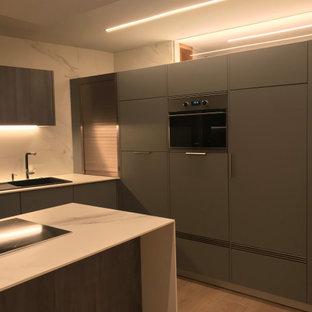 他の地域の中くらいのコンテンポラリースタイルのおしゃれなペニンシュラキッチン (シングルシンク、フラットパネル扉のキャビネット、グレーのキャビネット、タイルカウンター、白いキッチンパネル、磁器タイルのキッチンパネル、パネルと同色の調理設備、ラミネートの床、白いキッチンカウンター) の写真