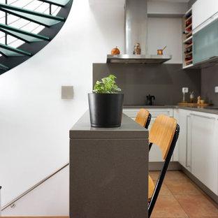 バルセロナの小さい北欧スタイルのおしゃれなキッチン (アンダーカウンターシンク、フラットパネル扉のキャビネット、白いキャビネット、クオーツストーンカウンター、グレーのキッチンパネル、大理石の床、シルバーの調理設備の、セラミックタイルの床、アイランドなし、オレンジの床、グレーのキッチンカウンター) の写真
