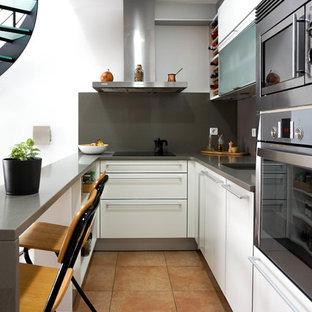Свежая идея для дизайна: маленькая угловая кухня в современном стиле с врезной раковиной, плоскими фасадами, белыми фасадами, столешницей из кварцевого агломерата, серым фартуком, фартуком из мрамора, техникой из нержавеющей стали, полом из керамической плитки, оранжевым полом, серой столешницей, обеденным столом и полуостровом - отличное фото интерьера