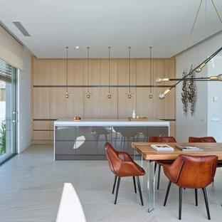 Foto de cocina lineal, actual, grande, abierta, con armarios con paneles lisos, puertas de armario de madera clara y una isla