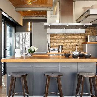 バルセロナのインダストリアルスタイルのおしゃれなキッチン (フラットパネル扉のキャビネット、グレーのキャビネット、木材カウンター、レンガのキッチンパネル、シルバーの調理設備の、無垢フローリング) の写真