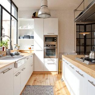 Idee per un'ampia cucina nordica con lavello a doppia vasca, ante bianche, top in legno, elettrodomestici in acciaio inossidabile e parquet chiaro