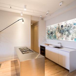 Modelo de cocina de galera, contemporánea, pequeña, con fregadero bajoencimera, armarios con paneles lisos, puertas de armario blancas, encimera de acero inoxidable, electrodomésticos de acero inoxidable, suelo de madera en tonos medios y una isla