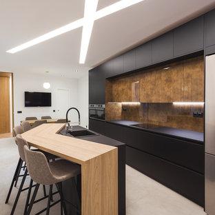 Modelo de cocina de galera, contemporánea, con armarios con paneles lisos, puertas de armario negras, electrodomésticos de acero inoxidable, una isla, fregadero encastrado, salpicadero marrón, salpicadero de vidrio templado, suelo gris y encimeras negras